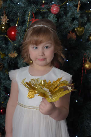 a girl in a white dress with a funny facial expression and a big Christmas gold flower by the Christmas tree Standard-Bild - 122690505