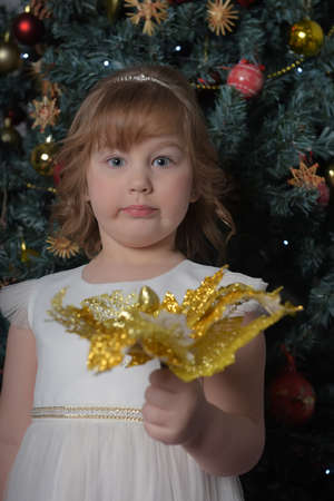 a girl in a white dress with a funny facial expression and a big Christmas gold flower by the Christmas tree Standard-Bild - 122690506
