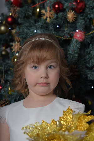 a girl in a white dress with a funny facial expression and a big Christmas gold flower by the Christmas tree Standard-Bild - 122690508