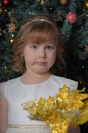 a girl in a white dress with a funny facial expression and a big Christmas gold flower by the Christmas tree Standard-Bild - 122690509