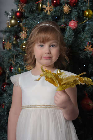 a girl in a white dress with a funny facial expression and a big Christmas gold flower by the Christmas tree Standard-Bild - 122690510