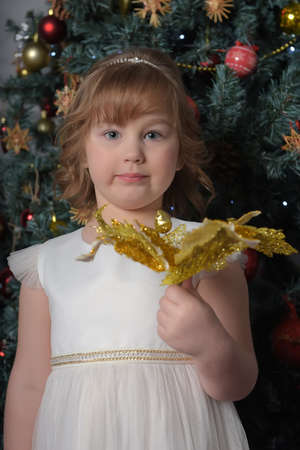 a girl in a white dress with a funny facial expression and a big Christmas gold flower by the Christmas tree Standard-Bild - 122690511