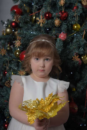a girl in a white dress with a funny facial expression and a big Christmas gold flower by the Christmas tree Standard-Bild - 122690516