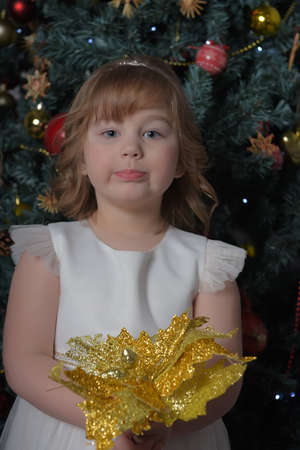 a girl in a white dress with a funny facial expression and a big Christmas gold flower by the Christmas tree Standard-Bild - 122690517