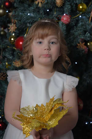 a girl in a white dress with a funny facial expression and a big Christmas gold flower by the Christmas tree Standard-Bild - 122690518