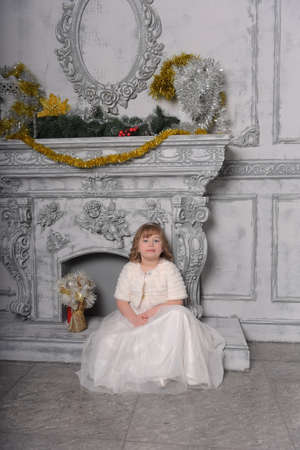 girl child in a white dress and a fur coat by the old fireplace in the interior
