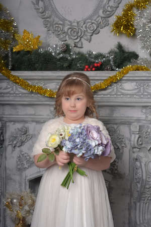 a girl child in a white dress and a fur coat with a wedding bouquet in her hands at the ceremony