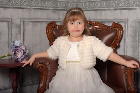 girl in a white dress and a fur coat sits in a leather chair