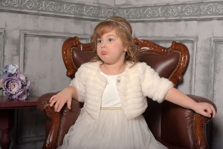 girl in a white dress and a fur coat sits in a leather chair Banco de Imagens
