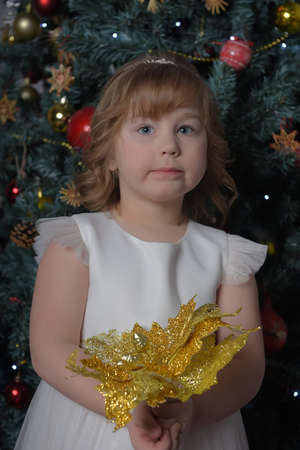 a girl in a white dress with a funny facial expression and a big Christmas gold flower by the Christmas tree Standard-Bild - 122690659