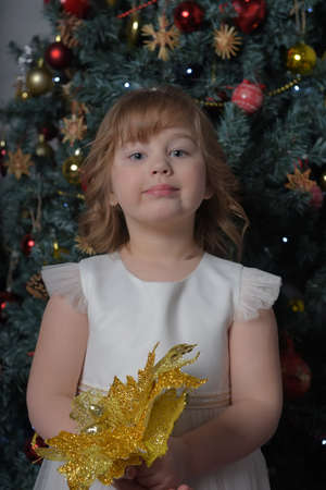 a girl in a white dress with a funny facial expression and a big Christmas gold flower by the Christmas tree Standard-Bild - 122690660