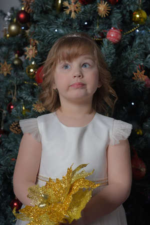 a girl in a white dress with a funny facial expression and a big Christmas gold flower by the Christmas tree Standard-Bild - 122690662