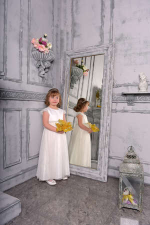 a girl in a white dress with a funny facial expression and a big Christmas gold flower at the mirror and a reflection in it Standard-Bild - 122689000