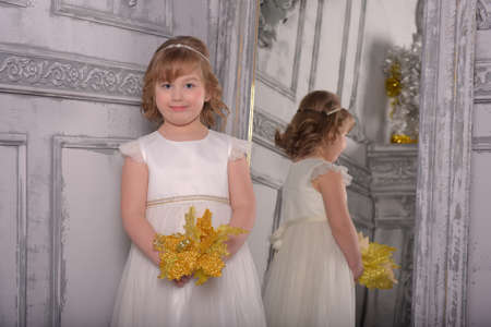 a girl in a white dress with a funny facial expression and a big Christmas gold flower at the mirror and a reflection in it Standard-Bild - 122689001