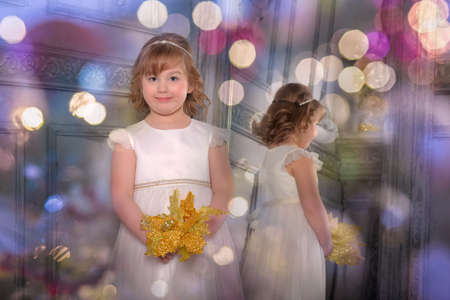 a girl in a white dress with a funny facial expression and a big Christmas gold flower at the mirror and a reflection in it Standard-Bild - 122689003