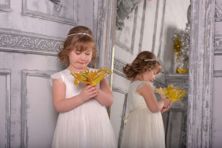 a girl in a white dress with a funny facial expression and a big Christmas gold flower at the mirror and a reflection in it Standard-Bild - 122689005