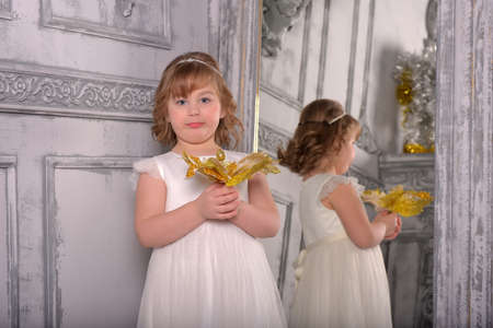 a girl in a white dress with a funny facial expression and a big Christmas gold flower at the mirror and a reflection in it Standard-Bild - 122689012