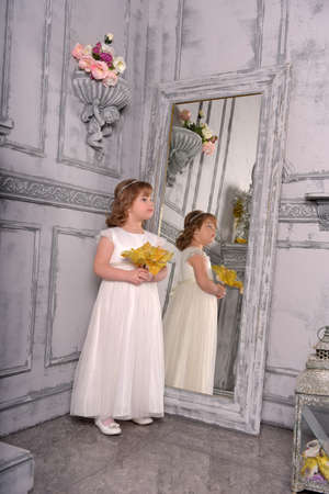 a girl in a white dress with a funny facial expression and a big Christmas gold flower at the mirror and a reflection in it Standard-Bild - 122689020
