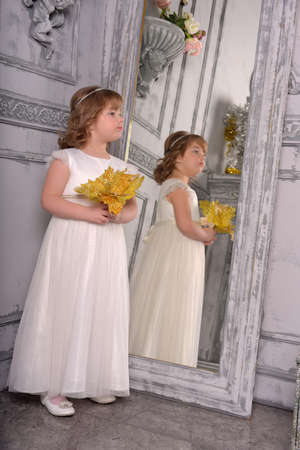 a girl in a white dress with a funny facial expression and a big Christmas gold flower at the mirror and a reflection in it Standard-Bild - 122689022