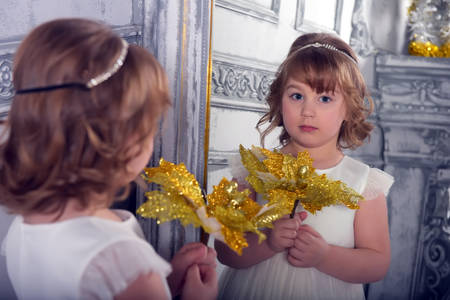 a girl in a white dress with a funny facial expression and a big Christmas gold flower at the mirror and a reflection in it Standard-Bild - 122689025