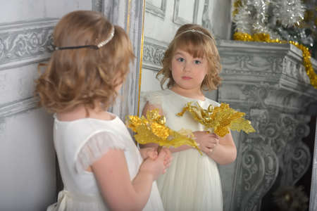 a girl in a white dress with a funny facial expression and a big Christmas gold flower at the mirror and a reflection in it