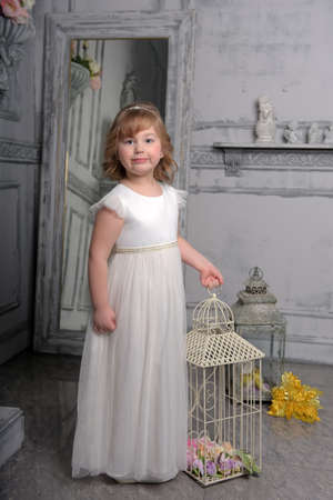 cute little girl with white dress near bird cage
