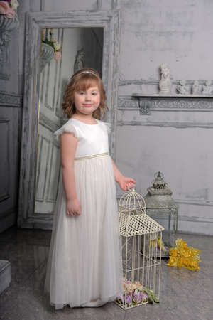 2039ae414446 cute little girl with white dress near bird cage Stock Photo - 122688899