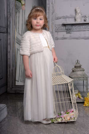 c1d2e5a2614b cute little girl with white dress near bird cage Stock Photo - 122688869