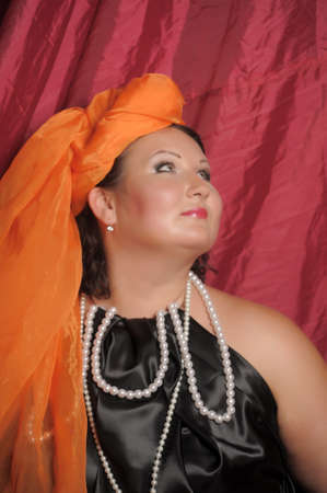 woman in oriental clothes in an orange scarf on her head Standard-Bild - 132544945