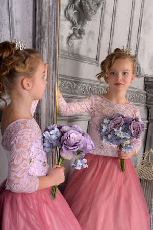 blonde with curls in a hairstyle princess with lilac flowers in her hands in the interior of a gray room in front of a mirror