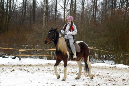 girl in a hat and jacket riding a horse in winter