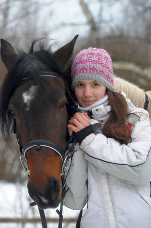 girl in a hat and jacket in winter with a horse Banco de Imagens