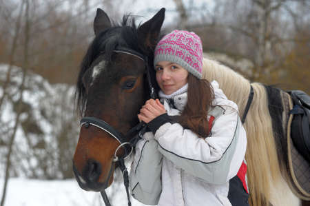 girl in a hat and jacket in winter with a horse Фото со стока