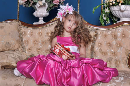 cute little girl in a pink dress among the flowers in the studio on the couch with a box in hands, birthday, holiday
