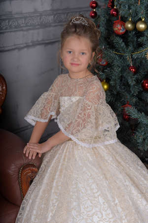 cute little girl in elegant white Victorian dress in the interior