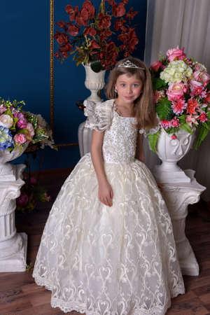 joven princesa con un vestido blanco y una diadema en el pelo entre flores