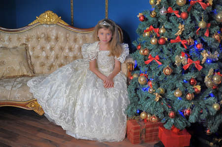 young princess in a white dress and a diadem in her hair sits in a chair