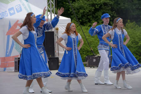 """Russia, St. Petersburg 25,05,2019 People in blue Russian national costumes dance at the International Festival """"Have Contact!"""""""