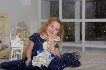 girl child blonde in a blue dress sitting on the bed with a flashlight and a Russian New Year's doll in a kokoshnik