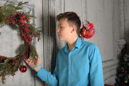 young teenager boy in blue shirt at christmas at the door with christmas wreath 스톡 콘텐츠