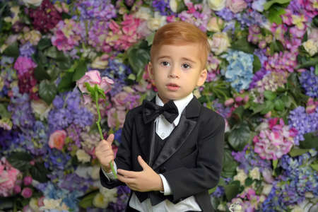 little boy in a tailcoat suit with a bow tie on the background of flowers with flowers in his hands