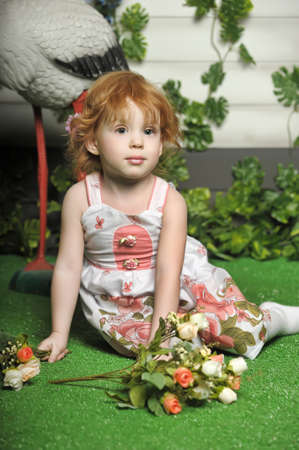 little red-haired girl in a white dress with a bouquet of flowers plays
