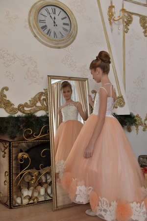 beautiful young girl with evening haircut in pink with white a lash by a gilded mirror, fitting, morning before the holiday
