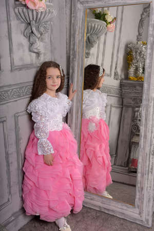 Princess girl in white with a pink dress near the mirror, reflection
