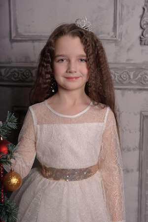 girl in ivory festive dress in christmas with a crown on her head Foto de archivo