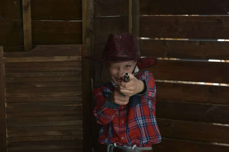 Boy brunette in a plaid shirt in a cowboy hat with a gun in the hands 写真素材
