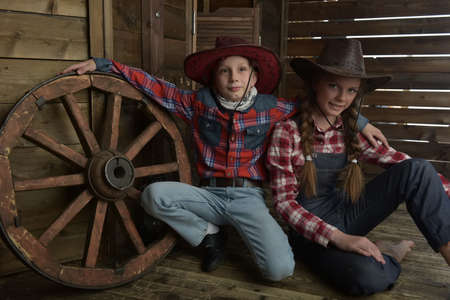Boy and girl, brother and sister in cowboy hats