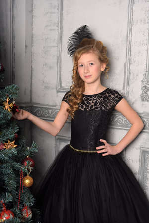 girl in elegant black dress with a feather in the evening hairstyle by the Christmas tree at Christmas Stock Photo