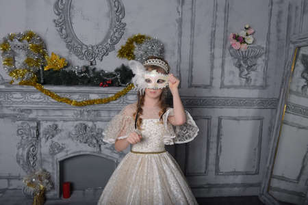 girl in elegant white dress and feather carnival mask