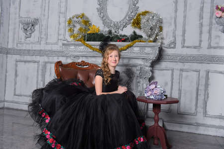 girl in a smart black dress in a chair by the fireplace